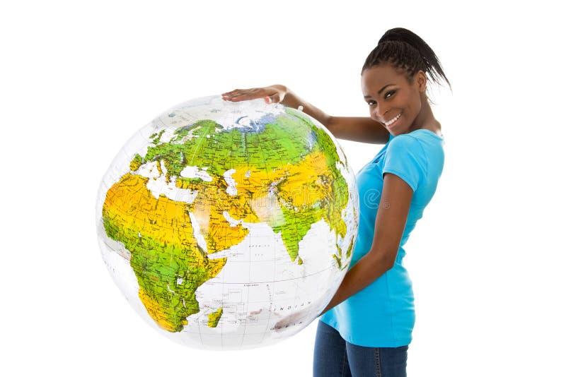 Jovem mulher colorida isolada que guarda um globo em suas mãos imagens de stock