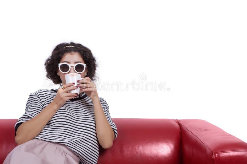 Jovem mulher com óculos de sol que bebe o café imagens de stock royalty free