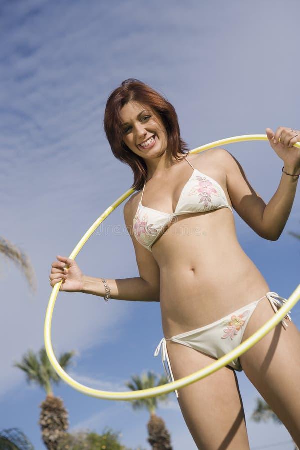 Jovem mulher com aro de Hula fotografia de stock royalty free