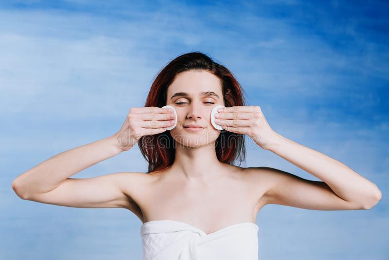 A jovem mulher com as almofadas de algodão do fundo do wihte de duas esponjas limpa a pele do problema com os olhos fechados fotografia de stock