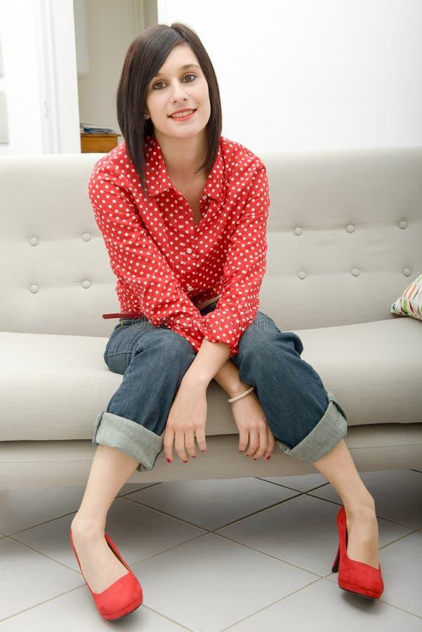 Jovem mulher com as calças de brim que sentam-se no sofá fotos de stock royalty free