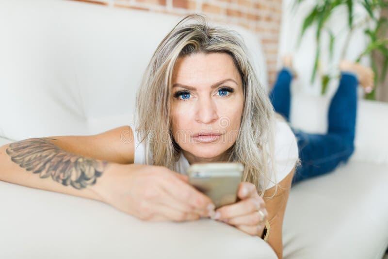 Jovem mulher com as lentes de contato azuis usando o telefone esperto fotos de stock royalty free