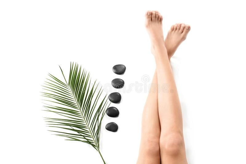 Jovem mulher com as pedras da folha de palmeira e dos termas no fundo branco, foco nos pés fotos de stock royalty free