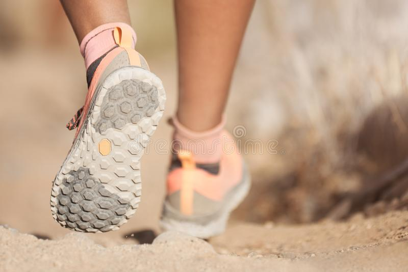 Jovem mulher com as sapatilhas atléticas que movimentam ou que correm a natureza imagem de stock royalty free