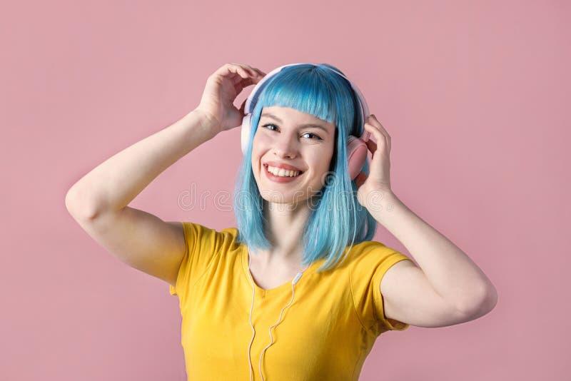 A jovem mulher com azul ouve-se para escutar a música imagens de stock