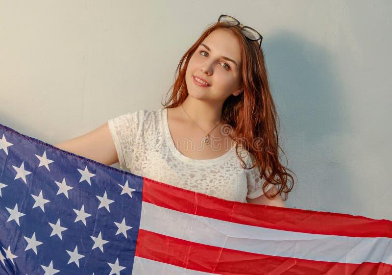 A jovem mulher com a bandeira americana nas mãos que olham o vintage da câmera coloriu a imagem imagem de stock