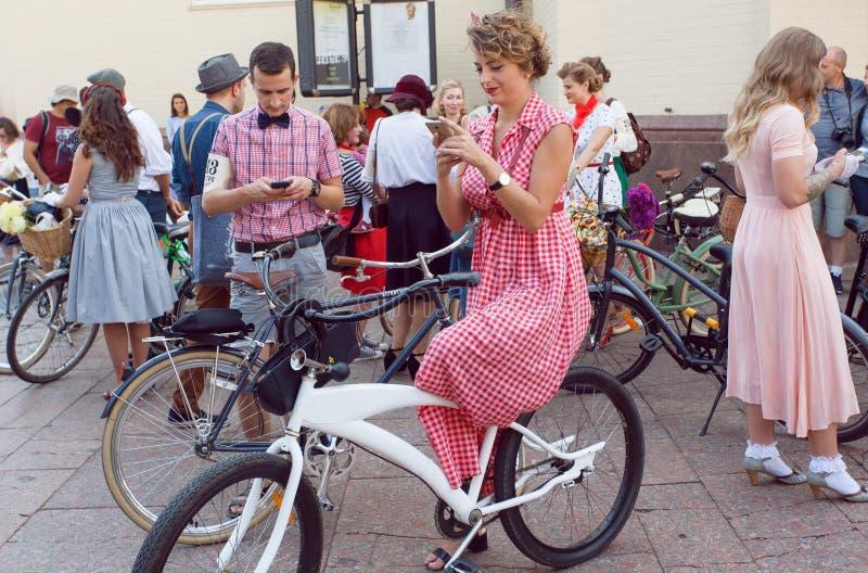 Jovem mulher com bicicleta que chama o telefone e que espera o começo do cruzeiro retro do festival foto de stock royalty free