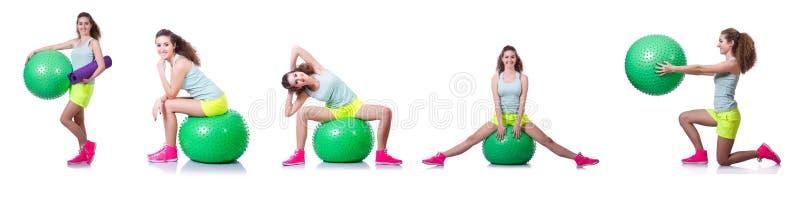 A jovem mulher com bola que exercita no branco foto de stock royalty free