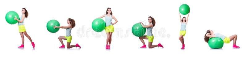 A jovem mulher com bola que exercita no branco foto de stock