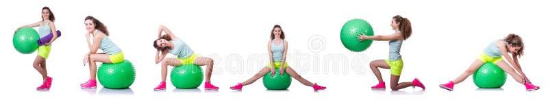 A jovem mulher com bola que exercita no branco fotos de stock