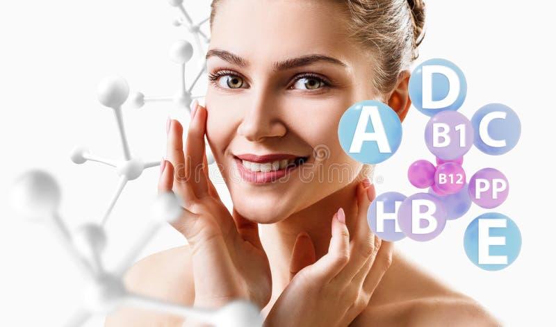 A jovem mulher com bolas das vitaminas aproxima a corrente da cara e das moléculas fotografia de stock