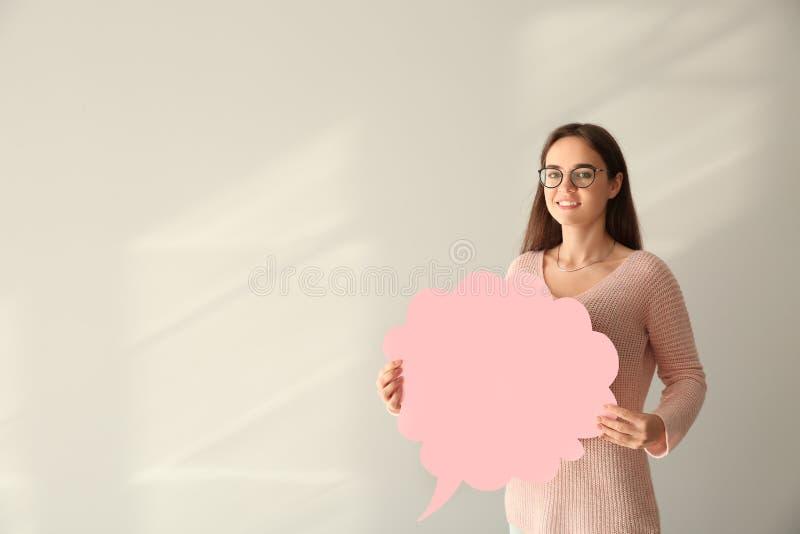 Jovem mulher com bolha vazia do discurso no fundo claro foto de stock