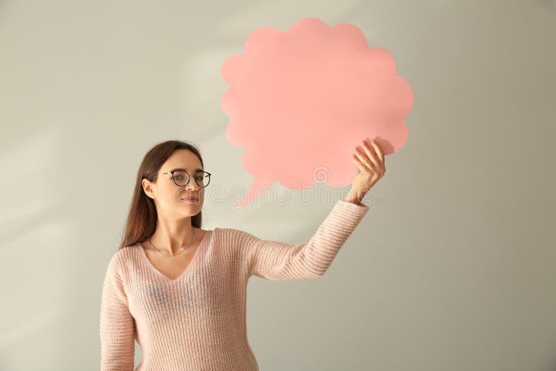 Jovem mulher com bolha vazia do discurso no fundo claro imagens de stock