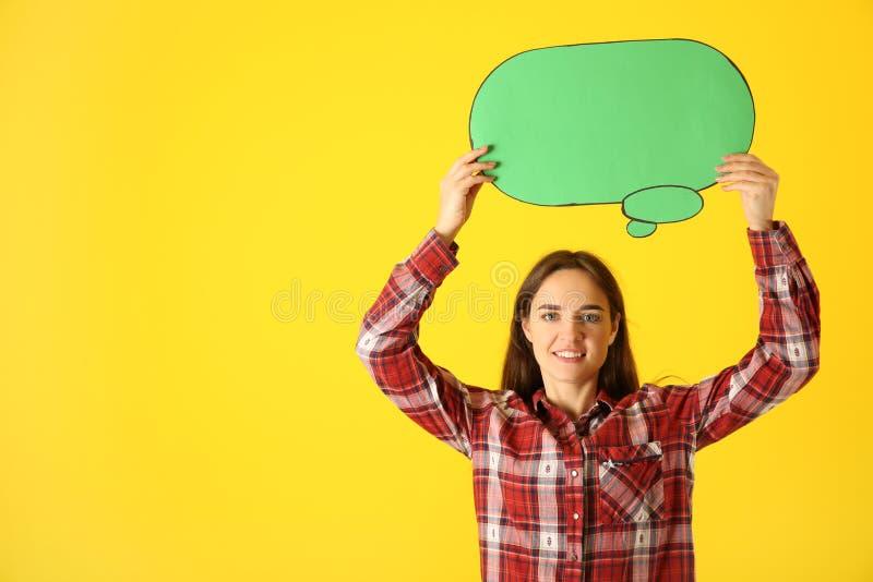 Jovem mulher com bolha vazia do discurso no fundo da cor fotos de stock