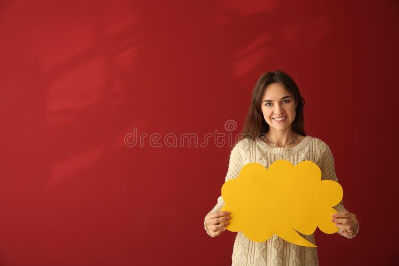 Jovem mulher com bolha vazia do discurso no fundo da cor foto de stock