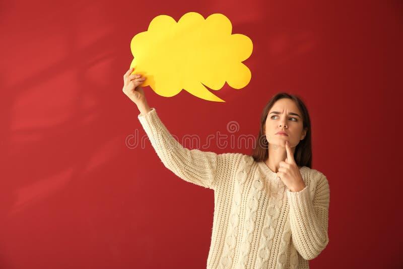Jovem mulher com bolha vazia do discurso no fundo da cor foto de stock royalty free