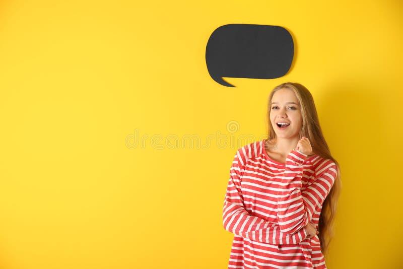Jovem mulher com bolha vazia do discurso no fundo da cor imagens de stock