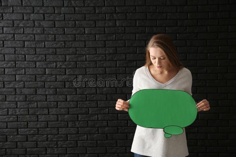 Jovem mulher com bolha vazia do discurso no fundo escuro fotografia de stock