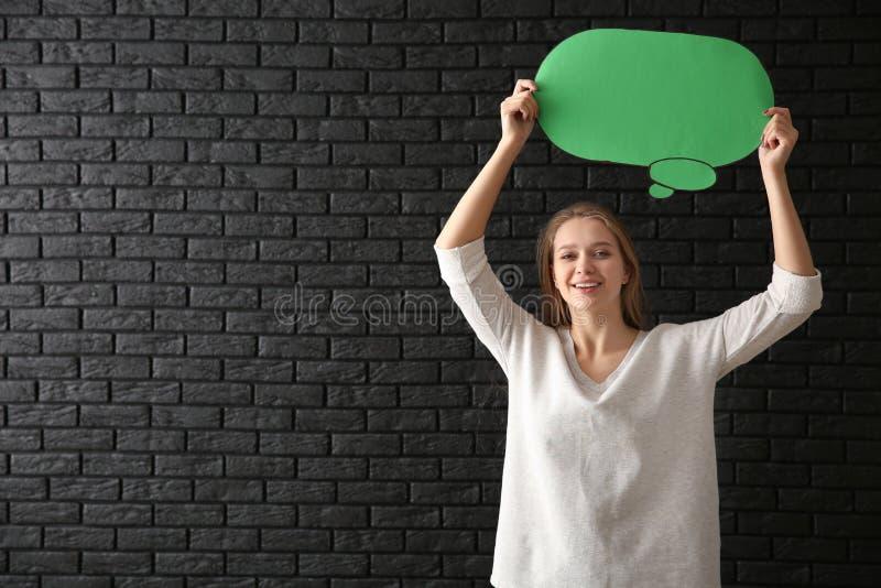 Jovem mulher com bolha vazia do discurso no fundo escuro fotos de stock royalty free