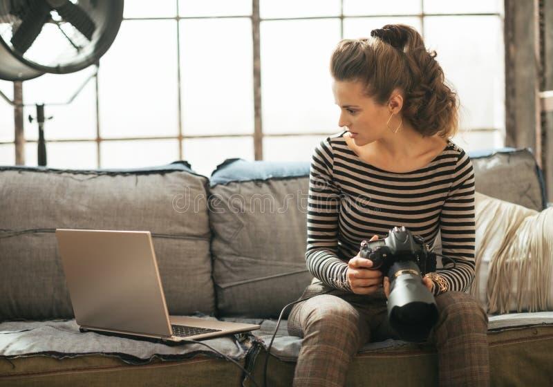 Jovem mulher com a câmera moderna do dslr usando o portátil fotografia de stock