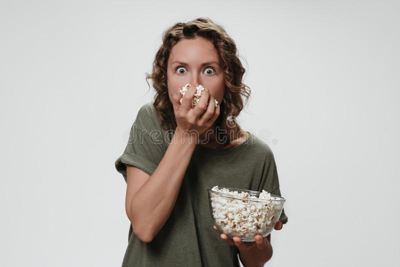A jovem mulher com cabelo encaracolado que come a pipoca, olha um filme de terror com grande surpresa fotografia de stock