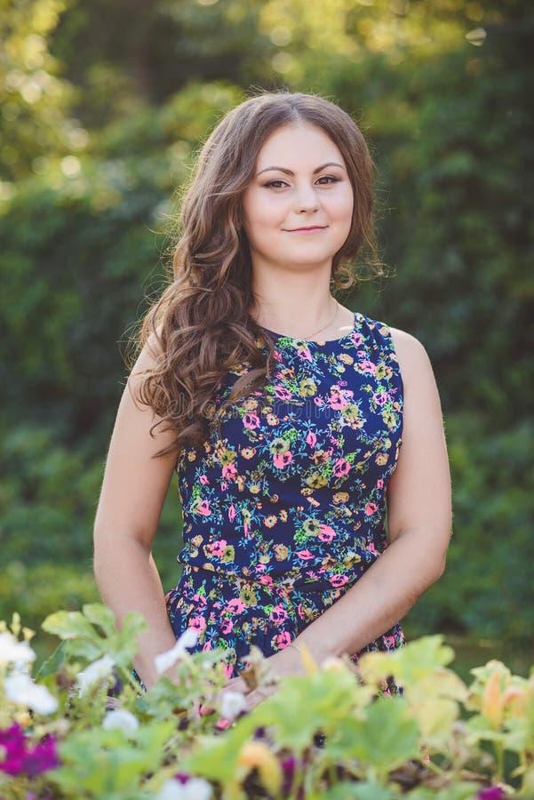 Jovem mulher com cabelo longo bonito no vestido floral perto dos carros de madeira decorativos com flores, em um fundo de fotos de stock