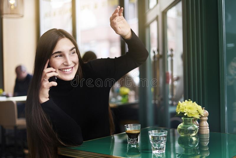 A jovem mulher com cabelo longo dá olá!-cinco a alguém, café da bebida que tem o resto no café perto do windowing foto de stock royalty free