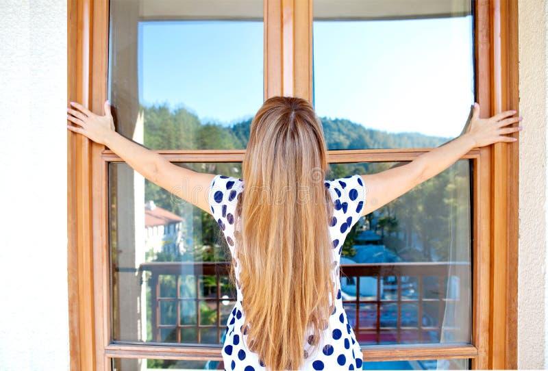 Jovem mulher com cabelo longo e a janela marrom de madeira fotografia de stock