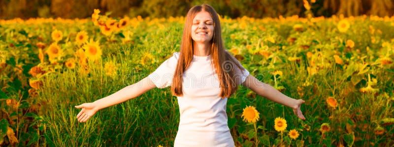 Jovem mulher com cabelo longo no campo do girassol com mãos acima Menina que aprecia fora a natureza imagem de stock