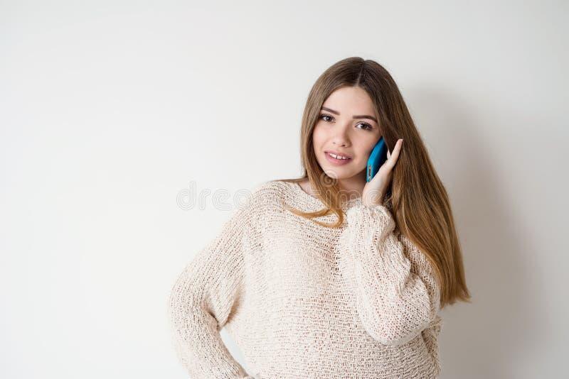 Jovem mulher com cabelo longo que fala no telefone foto de stock