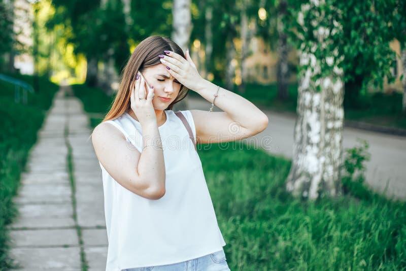 A jovem mulher com cabelo longo que fala no telefone celular e tem a dor de cabeça, guardando sua cabeça com a ajuda de suas mãos fotos de stock royalty free