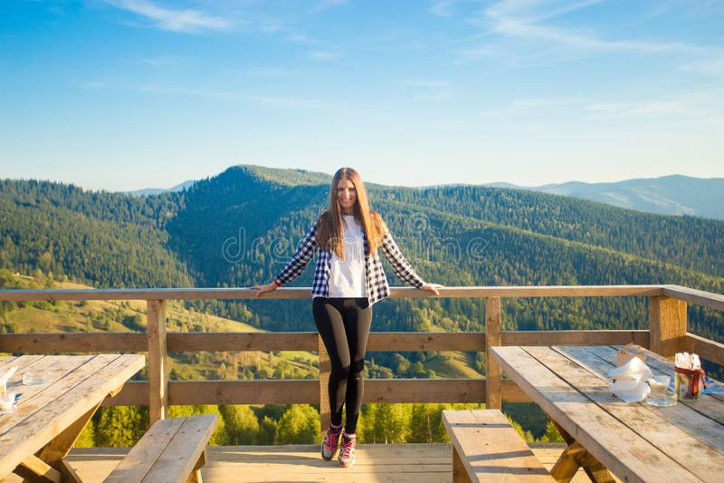A jovem mulher com cabelo longo tem o resto no café do ar livre sobre montanhas e aprecia a vista imagens de stock