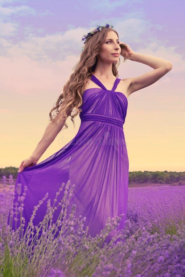 Jovem mulher com cabelo louro longo em um vestido roxo que olha t foto de stock