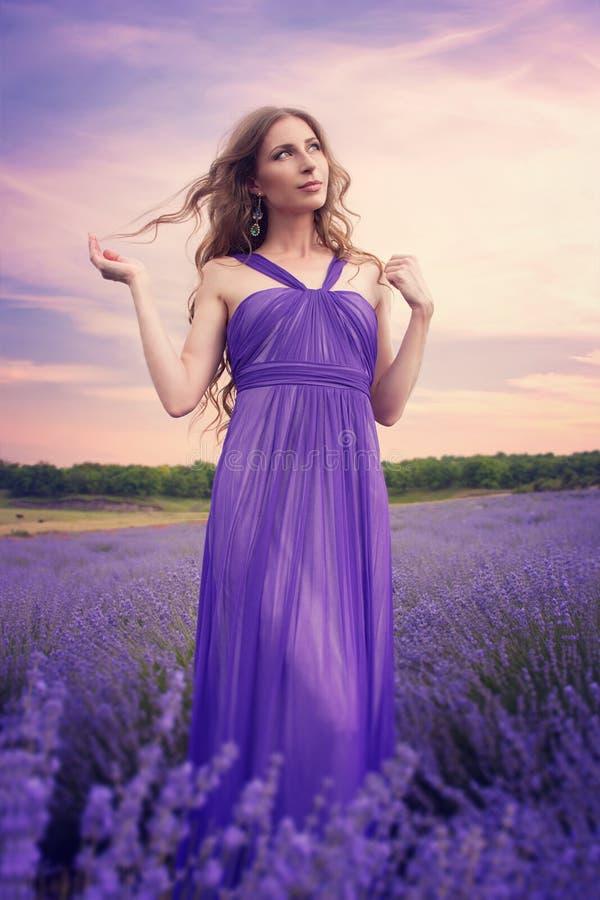 Jovem mulher com cabelo louro longo em um vestido roxo que olha t fotografia de stock royalty free