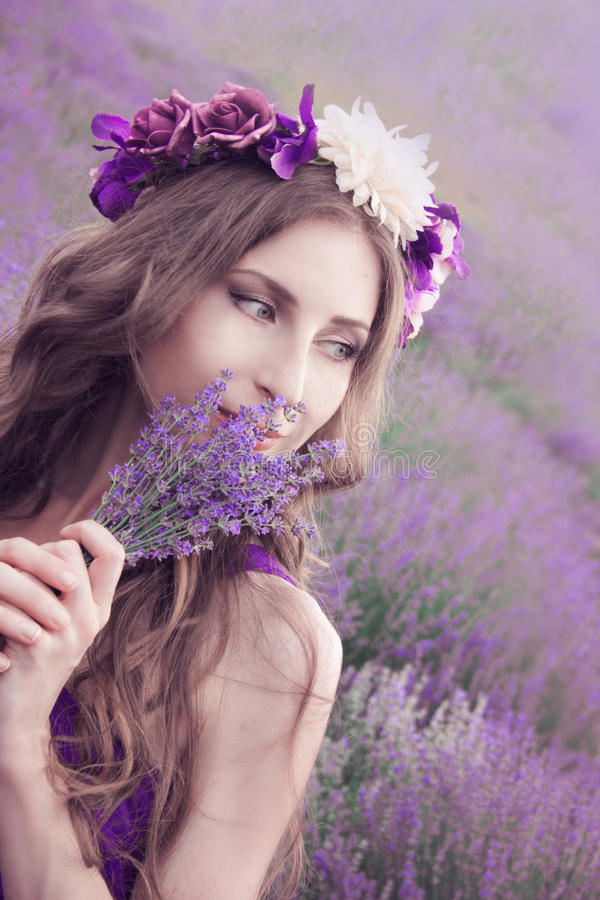 Jovem mulher com cabelo louro longo em uma apreciação roxa do vestido imagens de stock