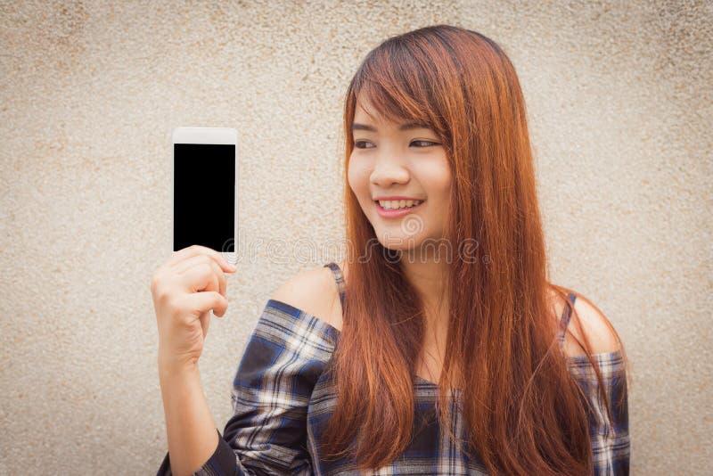 Jovem mulher com cabelo marrom que sorri mostrando uma tela vazia do smartphone que está no fundo do muro de cimento imagem de stock royalty free