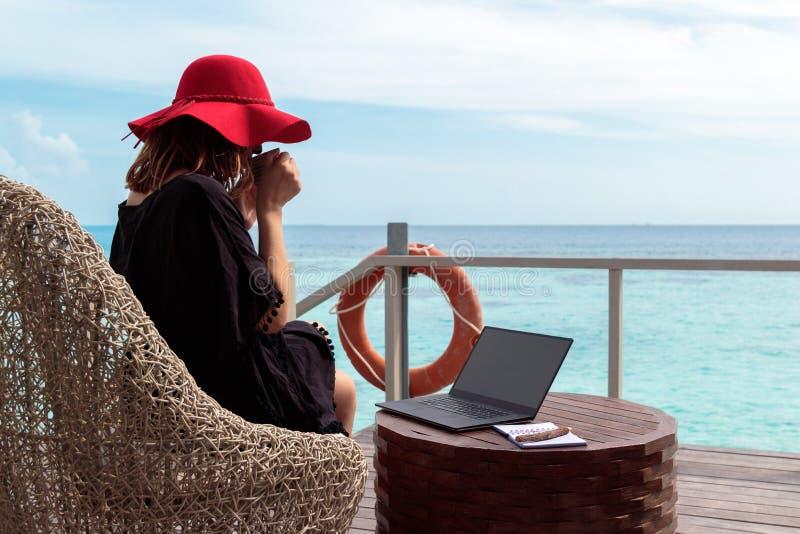Jovem mulher com café bebendo do chapéu vermelho e trabalho em um computador em um destino tropical imagem de stock