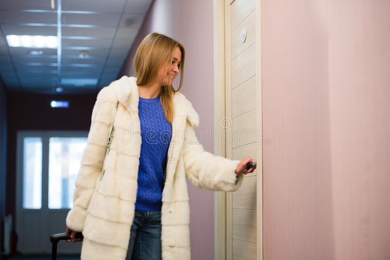 Jovem mulher com a camisa de manta e as calças de brim curtos que guardam uma mala de viagem e porta de abertura da sala de hotel imagem de stock royalty free