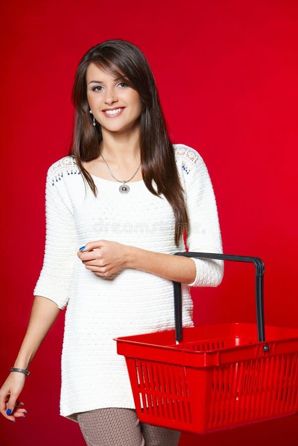 Jovem mulher com cesto de compras vermelho fotografia de stock