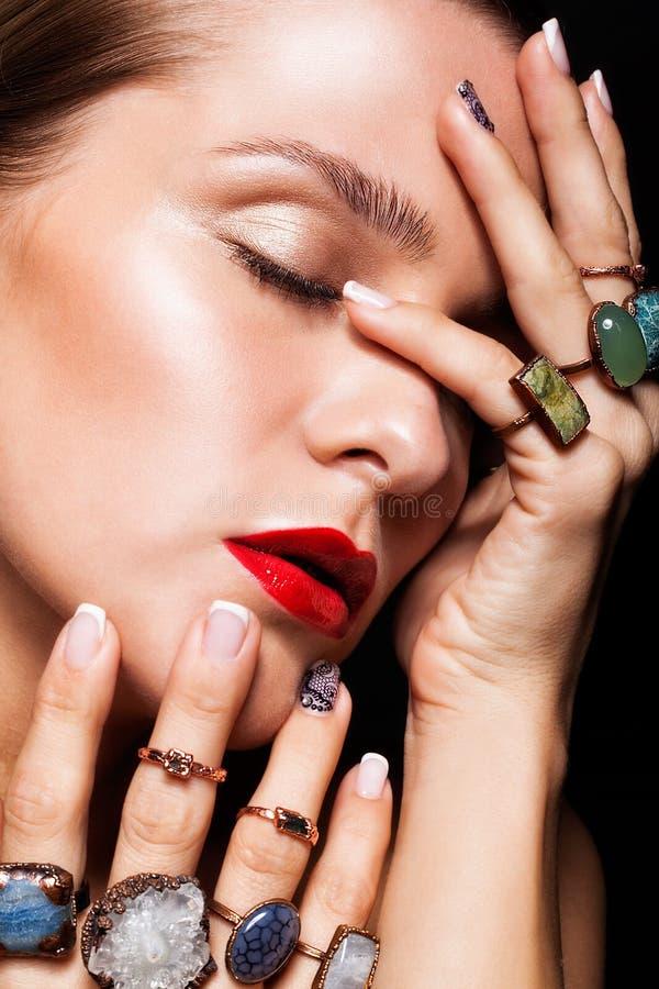 Jovem mulher com com muitos anéis do bijouterie com as pedras na aleta foto de stock