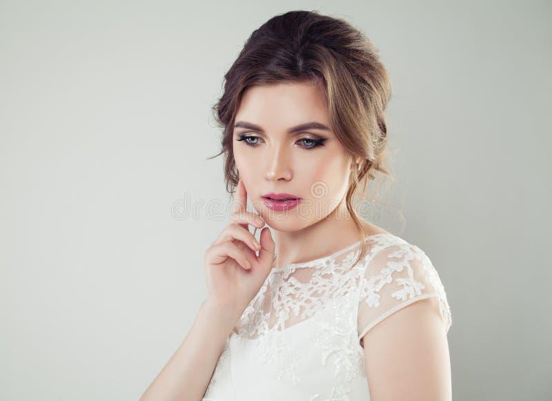 Jovem mulher com composição e penteado nupcial Noiva bonita da mulher que olha para baixo, close up da cara imagem de stock royalty free