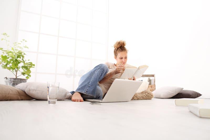 Jovem mulher com computador que lê um livro, encontrando-se no assoalho dentro imagens de stock royalty free