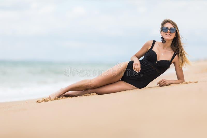 Jovem mulher com corpo perfeito no biquini que encontra-se na praia sobre o fundo azul do mar foto de stock