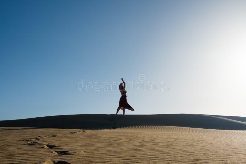 Jovem mulher com dança longa da saia na distância na maneira sugestiva e segura sobre a duna do deserto com o céu azul claro fotos de stock royalty free