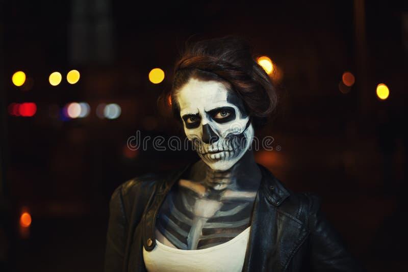 A jovem mulher com Dia das Bruxas enfrenta a arte Retrato da rua Fundo da cidade da noite Fim acima imagens de stock