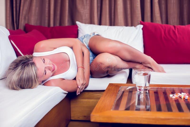 Jovem mulher com a dor de estômago que encontra-se no sofá Medicina e ele imagens de stock royalty free