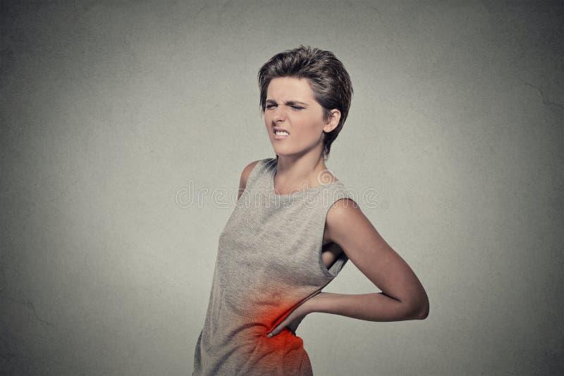 Jovem mulher com dor nas costas da dor lombar colorida para trás no vermelho fotos de stock
