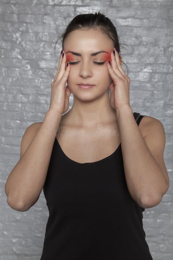 Jovem mulher com dores de cabeça da enxaqueca imagem de stock
