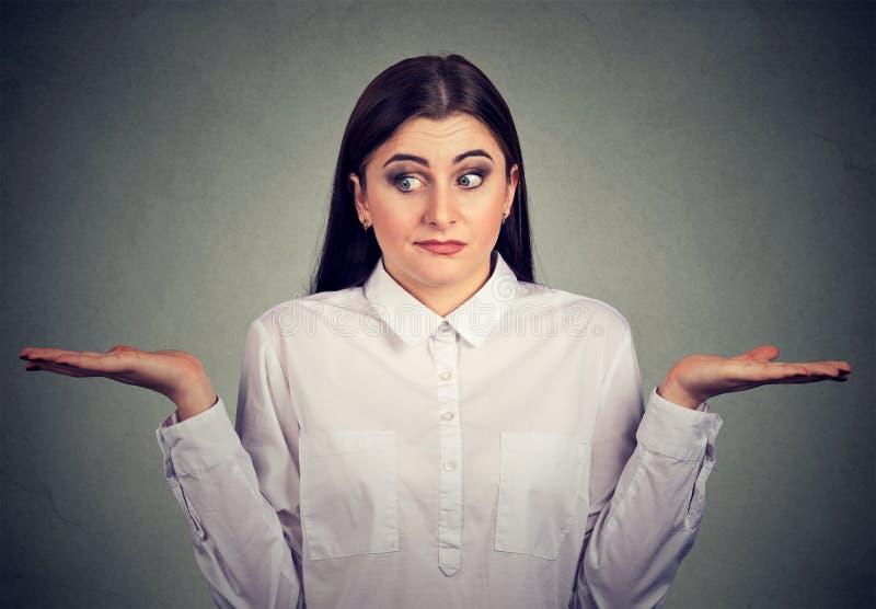 A jovem mulher com dos braços os ombros das encolhos de ombros para fora não tem nenhuma resposta fotografia de stock royalty free