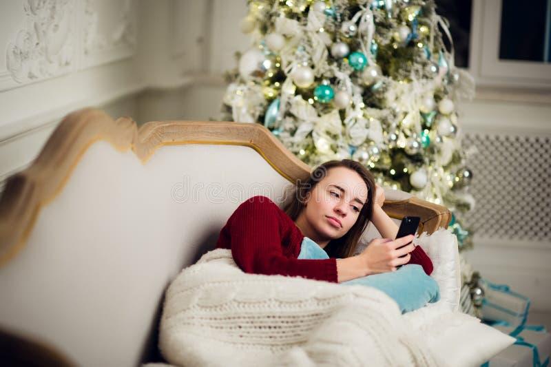 Jovem mulher com encontro home do telefone celular em um sofá na frente da árvore de abeto imagem de stock